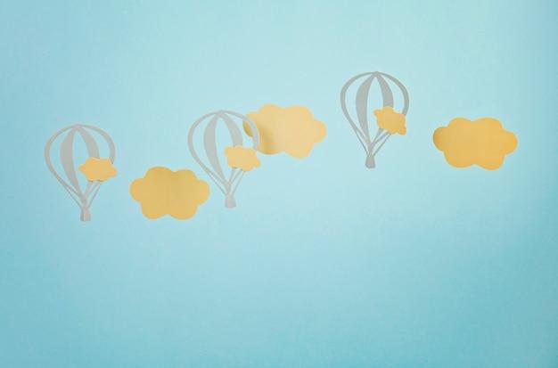 Mock-se com nuvens de papel e balões voando sobre fundo azul pastel