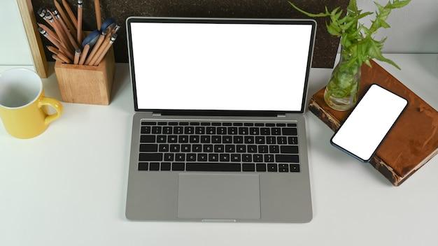 Mock-se computador portátil e telefone inteligente com tela em branco na mesa do escritório.