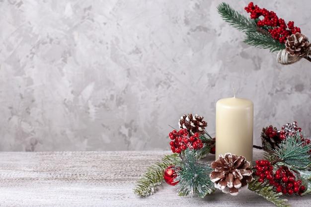 Mock-se de duas velas de natal grossas de baunilha bege e coroa de cones, bagas vermelhas e ramo.