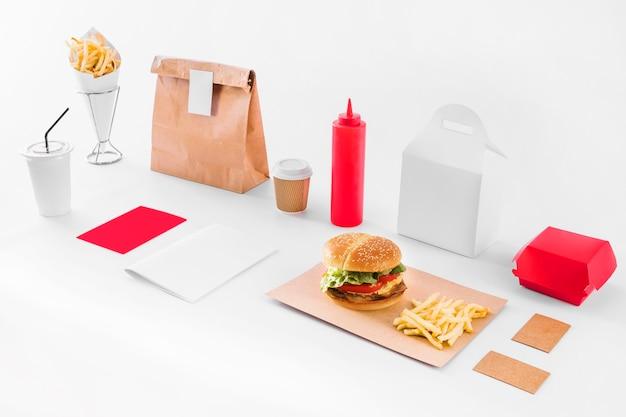 Mock-se de hambúrguer; batatas fritas; parcela; garrafa de molho e copo de eliminação no pano de fundo branco
