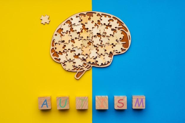 Mock-se de um cérebro humano com peças de quebra-cabeça espalhadas em um fundo amarelo e azul.