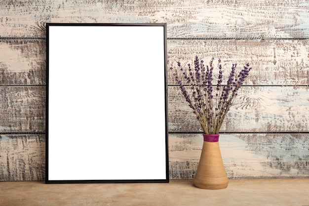 Mock-se de um pôster de moldura vazia em uma parede de tábuas de madeira. cacho de lavanda em um vaso