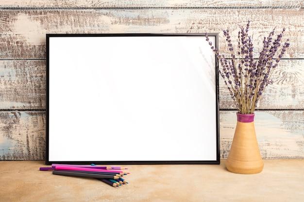 Mock-se de um pôster de moldura vazia em uma parede de tábuas de madeira. ramo de alfazema em um vaso e lápis de cor na mesa