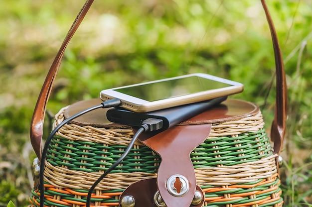 Mock-se de um smartphone com carregamento de power bank em uma cesta na floresta. conceito sobre o tema da recreação ao ar livre.