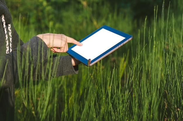 Mock-se de um tablet com um dedo perto da tela no fundo de uma bela natureza verde.