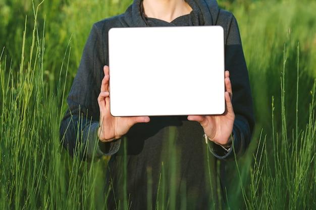 Mock-se de um tablet sem moldura moderno nas mãos de uma garota ao ar livre.