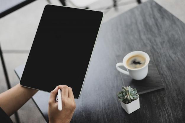 Mock-se de uma mulher segurando o dispositivo tablet digital nas mãos com lápis digital.