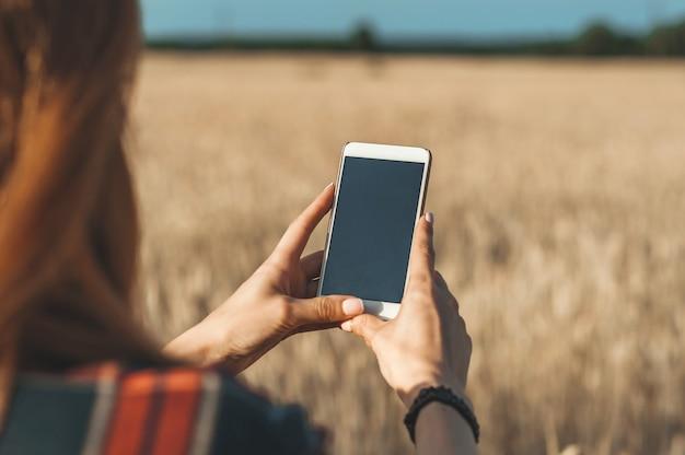 Mock-se do smartphone na mão da menina, no fundo do campo.