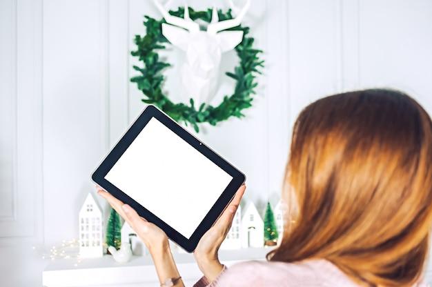 Mock-se do tablet nas mãos da menina. no fundo da parede com um cervo decorativo e uma coroa de flores com casas de festivo.