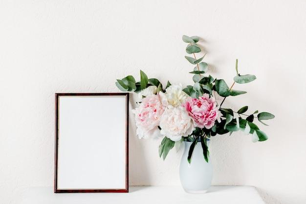 Mock-se frame frame com um buquê de peônias em um vaso.