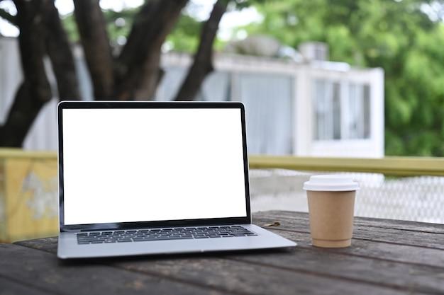 Mock-se, laptop, computador e xícara de café na mesa de madeira ao ar livre.
