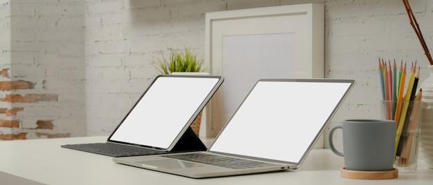Mock-se laptop e tablet digital com teclado na mesa de trabalho moderna com artigos de papelaria e decorações