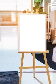 Mock-se outdoor de publicidade em branco branco para o café do restaurante da frente do quadro de menu com um vaso de plantas. folhas de livreto de suporte, cartão de barraca de papel no refeitório de mesa exibem o texto de inserção de plano de fundo do produto.