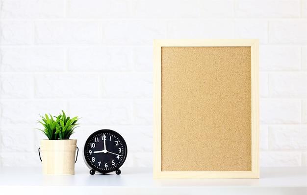 Mock-se placa de cortiça em branco com relógio, plantas verdes na parede de tijolo branco, estilo minimalista