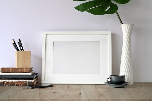 Mock-se quadro na mesa e gadget de escritório em casa.