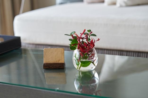 Mock-se rótulo stand com vaso de água de flor na mesa na sala para o conceito de recepção de boas-vindas