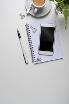 Mock-se smartphone, caderno, xícara de café, planta e copie o espaço na mesa de escritório branca.