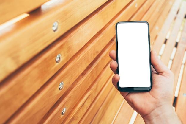Mock-se smartphone nas mãos de um homem, sobre um fundo de uma parede de madeira.