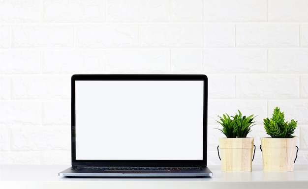 Mock-se tela de laptop em branco com plantas verdes na parede de tijolo de sala branca