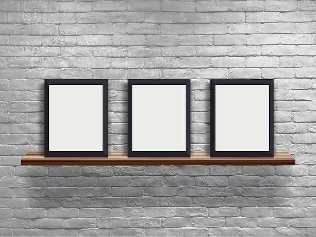 Mock-se três quadro em branco na prateleira de madeira com parede de tijolo branco