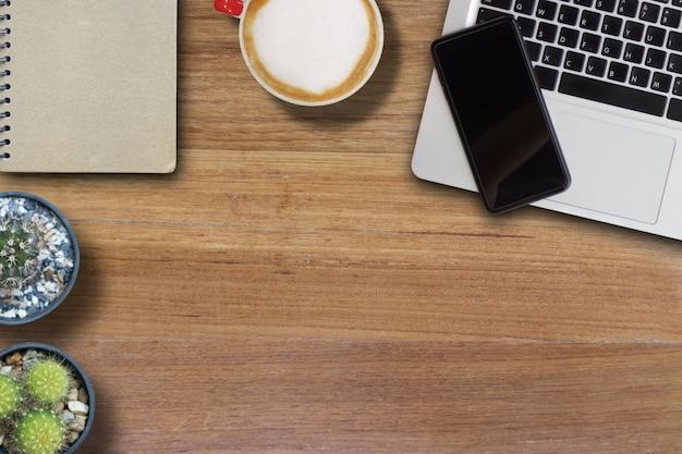 Mock up celular no laptop e café quente e capa de livro de marrom e cacto