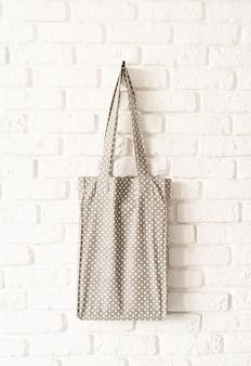 Mock up cinza pontilhada tote bag eco hipster branco tecido de algodão no fundo da parede de tijolo branco. copie o espaço