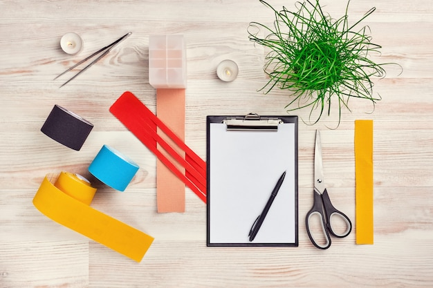 Mock up com prancheta, rolos de fita kinesio colorido, tesoura, pinça e outras ferramentas médicas