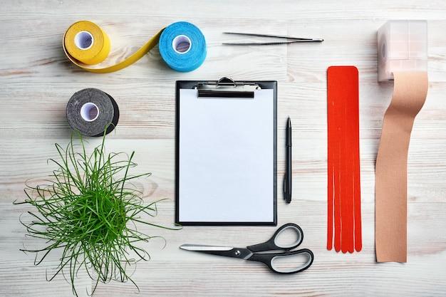 Mock up com prancheta, rolos de fita kinesio colorido, tesoura, pinça e outras ferramentas