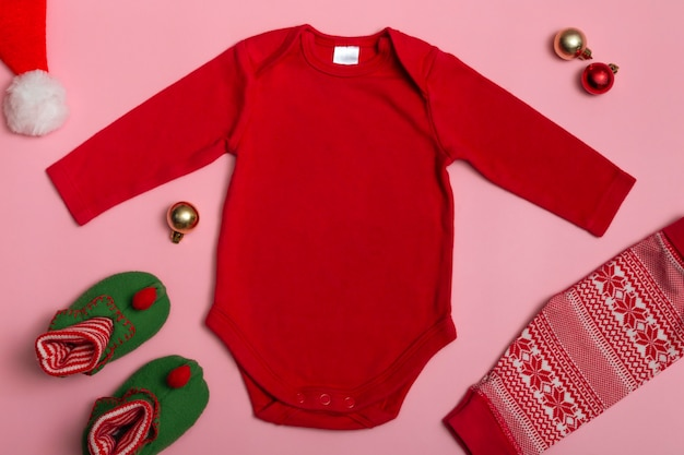 Mock up de um body de bebê de reveillon com mangas compridas em vermelho sobre fundo rosa, decorado com chinelos de gnomo, calças vermelhas e enfeites de natal, vista de cima.
