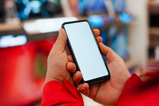 Mock-up de um smartphone com tela branca nas mãos de um homem. telefone no espaço das tvs da loja.