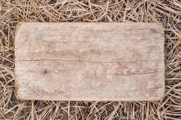 Mock up é a placa de madeira no fundo de uma grama seca de outono. layout para escrever o texto da mensagem e adicionar itens