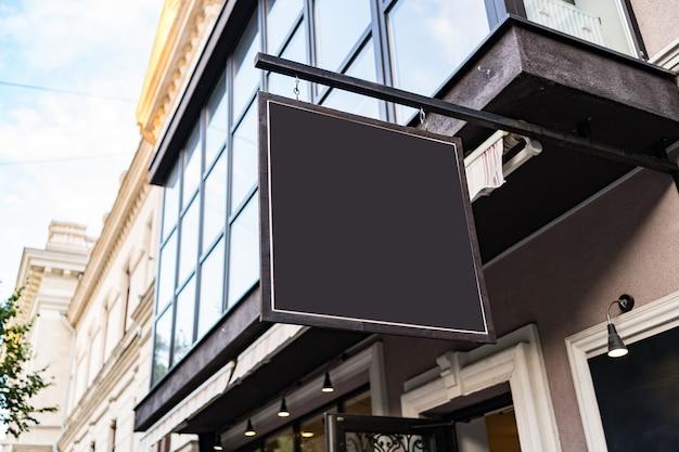 Mock up em branco do design da tabuleta do café em um prédio agradável ao ar livre