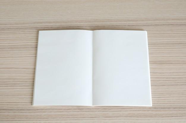 Mock up em branco livro de papel aberto na mesa de madeira