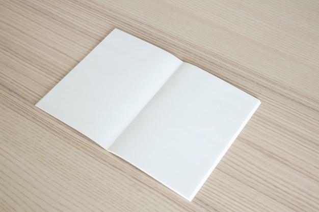 Mock up em branco livro de papel aberto no fundo da mesa de madeira