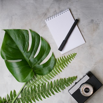 Mock up espaço de trabalho com folha de palmeira tropical, notebook, câmera, caneta, cartão e xícara de café