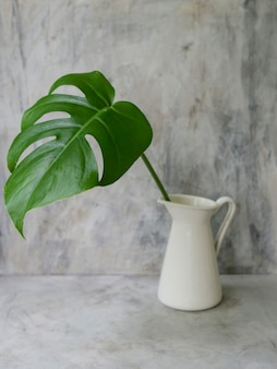 Mock up espaço de trabalho com folha tropical em um vaso no fundo cinza