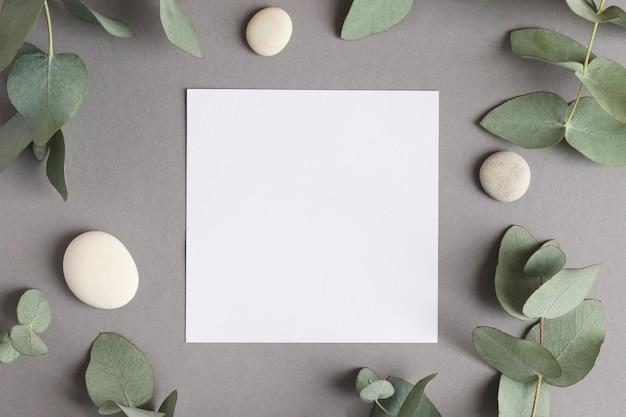 Mock up floral natural. papel em branco com folhas de eucalipto e pedras na textura cinza