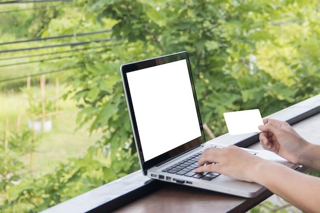 Mock up laptop e cartão de crédito na mão da mulher