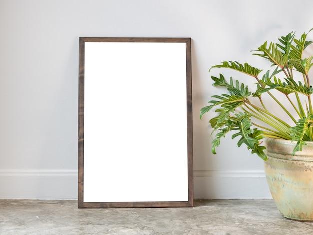 Mock up poster com moldura de madeira e planta de casa de philodendron xanadu em um lindo vaso de cerâmica verde situado em uma moderna sala de estar elegante com piso de cimento e parede branca.
