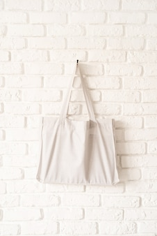 Mock up sacola de tecido de algodão branco sobre fundo de parede de tijolo branco. copie o espaço