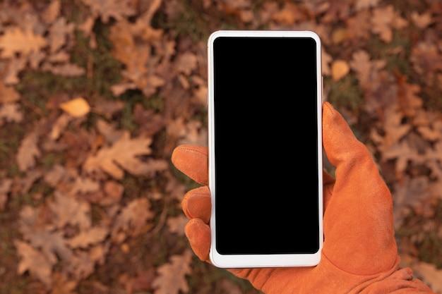 Mock-up telefone na mão em uma luva laranja contra o fundo de folhas caídas de outono