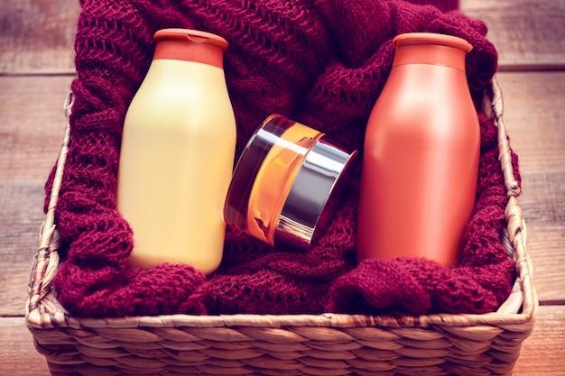 Mock-ups de garrafas com creme corporal e shampoo em uma camisola