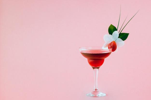 Mocktail decorado com morango, flor e folhas tropicais, foco seletivo.