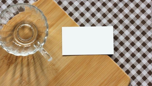 Mockup, criador de cena. cartão vazio, copo de vidro e tábua de corte de bambu em uma toalha de mesa quadriculada, vista superior. mesa da cozinha. copie o espaço.