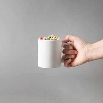 Mockup da mão segurando uma caneca de cereais coloridos