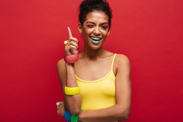 Moda alegre modelo feminino americano africano na camisa amarela, sorrindo e apontando o dedo para cima, isolado sobre a parede vermelha