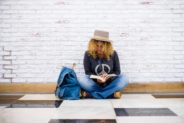 Moda alternativa, viagens pessoas, estilo de vida, linda moda encaracolada, mulher adulta sentar no chão e ler um livro com sua mochila azul