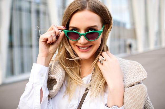 Moda ao ar livre fechar o retrato de uma deslumbrante mulher loira de negócios, sorrindo e olhando para a câmera, casaco de caxemira, óculos de sol olho de gato vintage, joias, cores suaves.