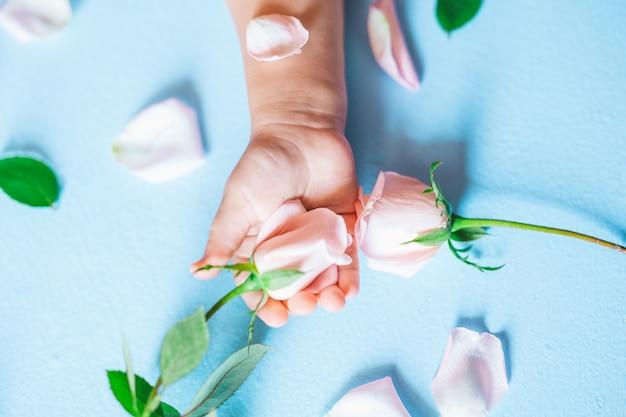 Moda arte mão de uma criança pequena segurando flores sobre fundo azul