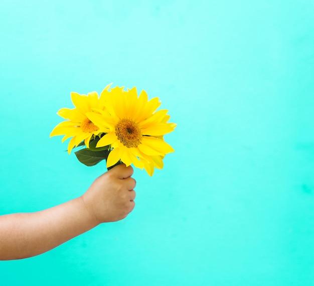 Moda arte mão de uma criança segurando a flor do sol amarelo